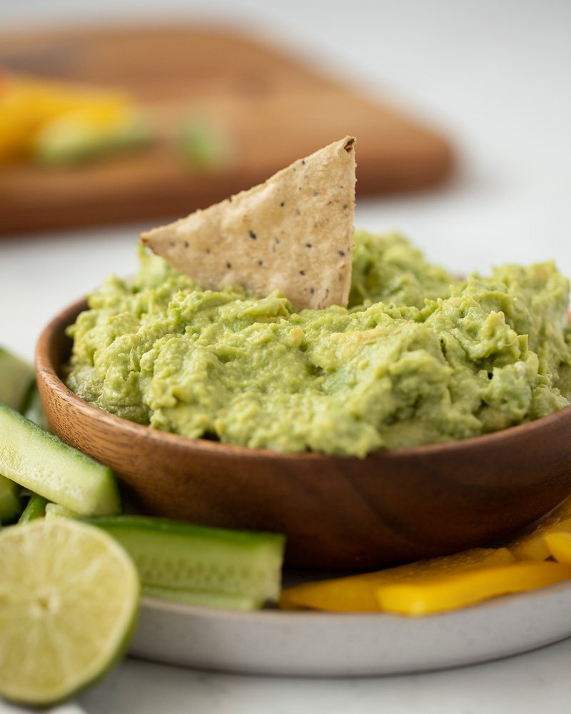 close up of wood bowl with 4 ingredient guacamole with single chip dipped in. White pale underneath with sliced cucumber and red pepper. Half lime on left and wood cutting cboard with veggies in background