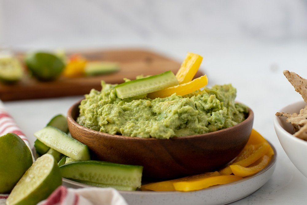 wood bowl with guacamole topped with sliced cucumber and yellow pepper on white plate with sliced veggies. Lime wedges in front left. Cutting board with veggies and lime in background.