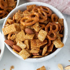 overhead view of white bowl with gluten-free chex mix. part view of bowls on left and napkin in upper right