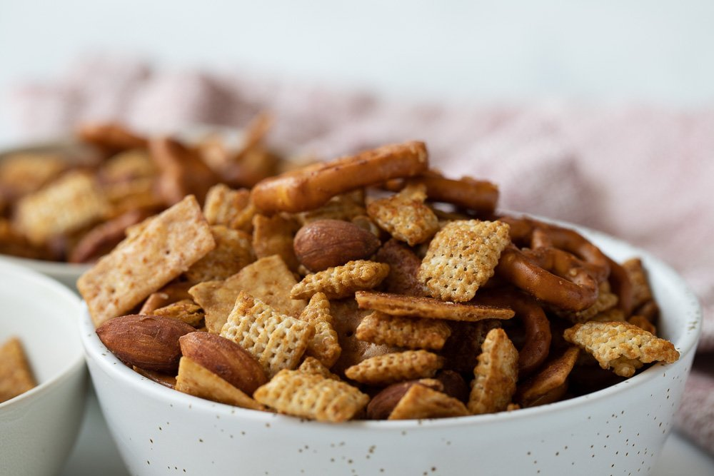 close up of white bowl with gluten-free chex mix snack. bowl and red napkin in background.