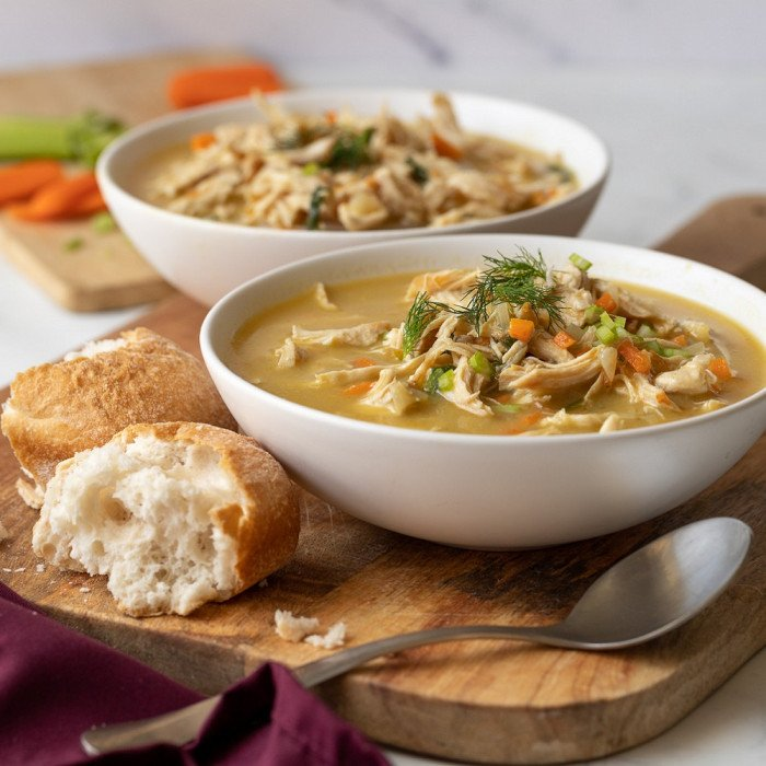 2 white bowls with gluten-free cream of chicken soup on wood board. Spoon and bread roll in front. Cutting board with celery and carrot in background