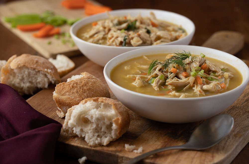 2 white bowls with gluten-free cream of chicken soup on wood board. Spoon and bread roll in front. Cutting board with celery and carrot in back