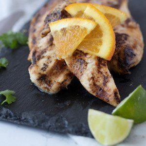 close up of grilled chicken with orange marinade on dark stone plate. Slice orange garnish, Fresh cilantro on left, lime wedges in front.