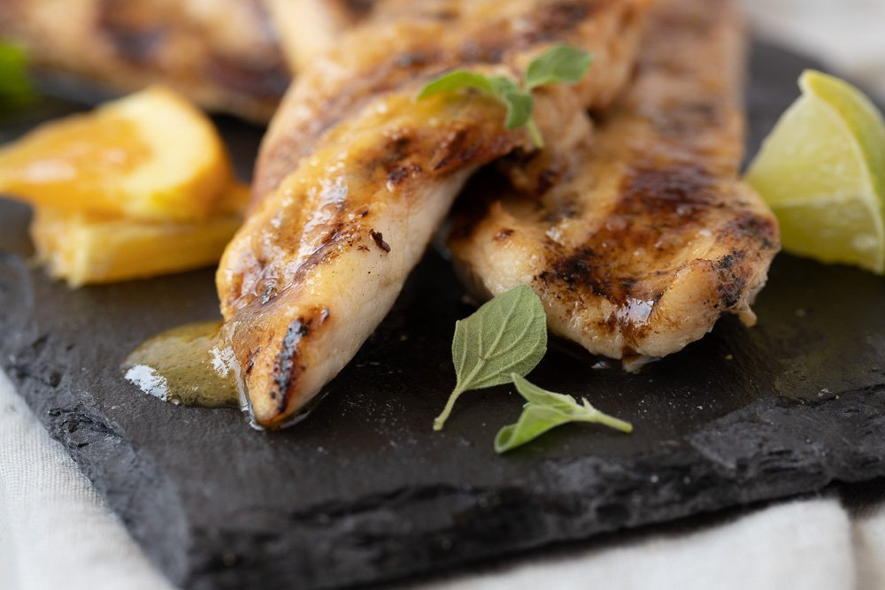close up of grilled chicken with orange marinade on dark stone plate.Orange slices on left, lime wedges on right. fresh oregano garnish