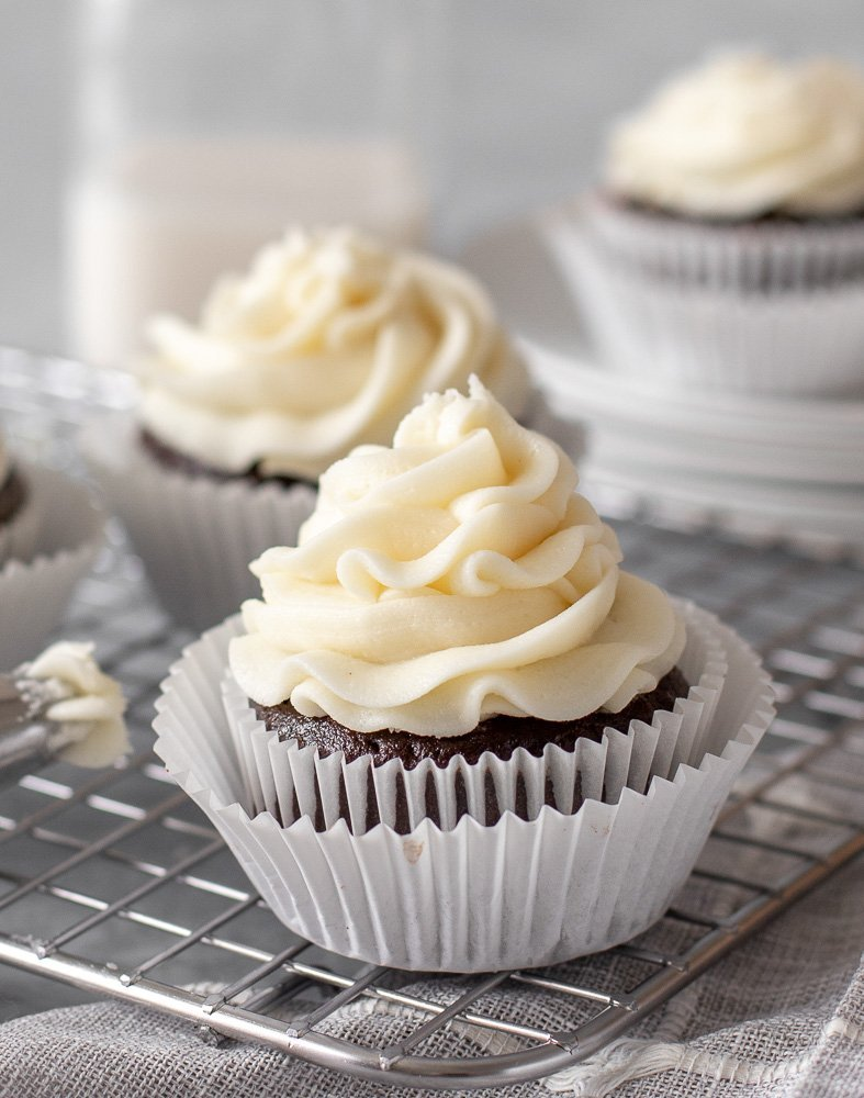 close up of gluten free chocolate cupcake with pipeable cream cheese frosting on wire rack. Cupcakes, milk bottle and stack of plates in background.