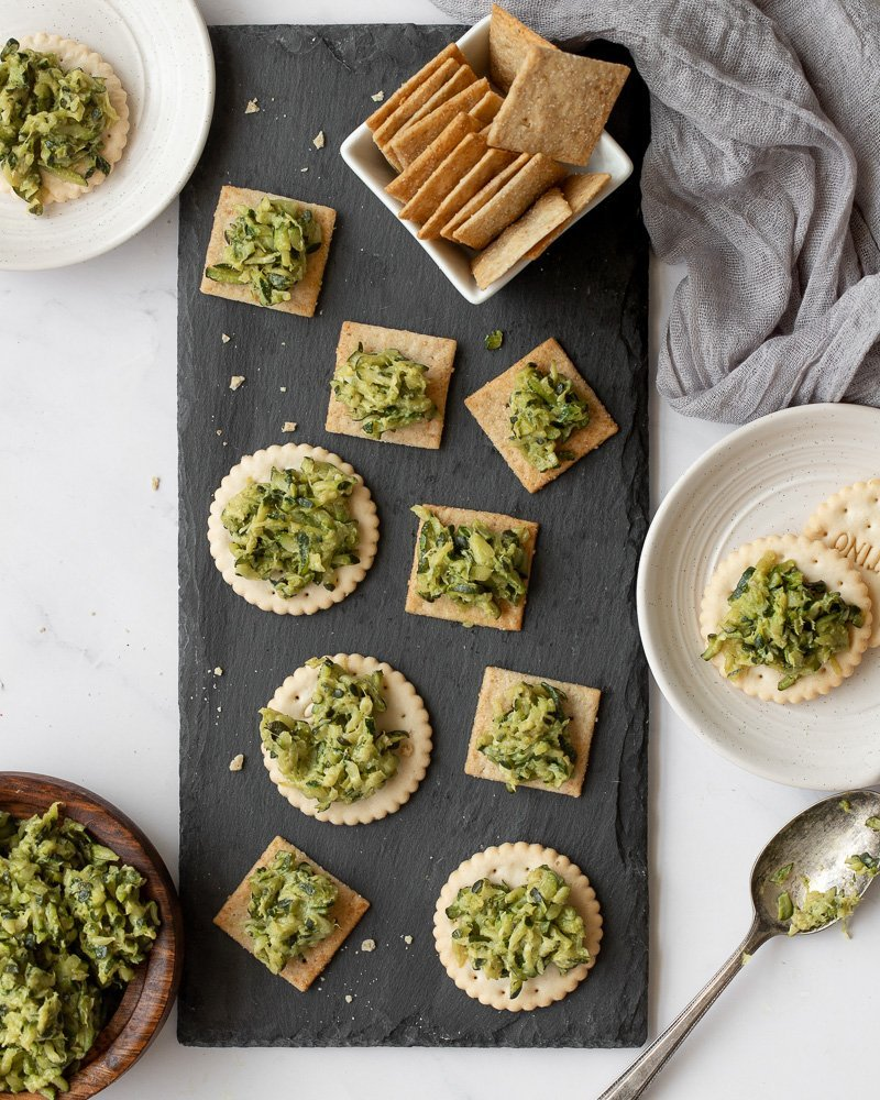 overhead view of slate platter with crackers with healthy sautéed shredded zucchini dip. Wood bowl with dip in lower left, spoon and small plate with crackers and dip on right. Gray napkin in upper right.