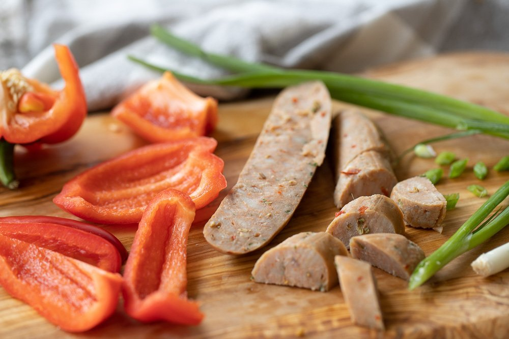 Wood board with sliced red bell pepper, cut Italian sausage and green onion.