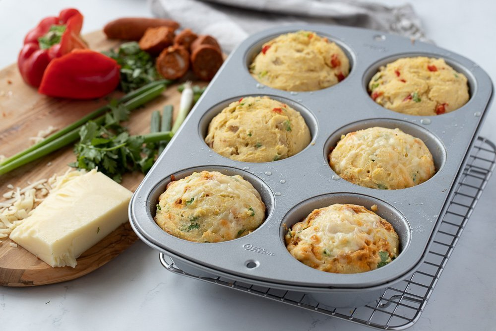 Jumbo muffin tin with gluten free breakfast muffins. Wood board with green onion, block of chees, bell pepper, chorizo and cilantro on left.