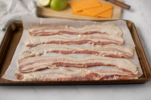 Strips of uncooked bacon on parchment lined baking sheet. Cutting board with cheddar cheese and green apple in background.