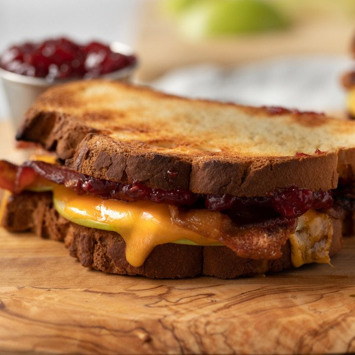 gluten free breakfast sandwich with melted cheddar, bacon, apple and jam on wood board. small bowl of jam and cutting board with green apple in background.
