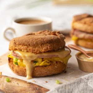 gluten free breakfast sandwich on english muffin with egg, canadian bacon and sauce dripping on parchment and wood board. Small wood bowl with sauce on right, coffee cup in back. White background,