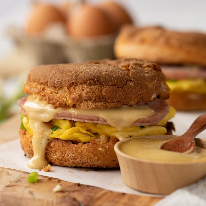 Gluten free breakfast sandwich on English muffin with egg, canadian bacon and sauce dripping on parchment and wood board. Small wood bowl with sauce on right, egg carton in back. White background,