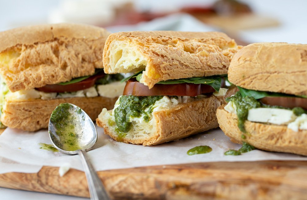 3 gluten free breakfast sandwiches on baguette with feta, tomato, spinach and pesto on parchment on top of wood board. Spoon with pesto in front. Cutting board with sliced tomato in back. white background.