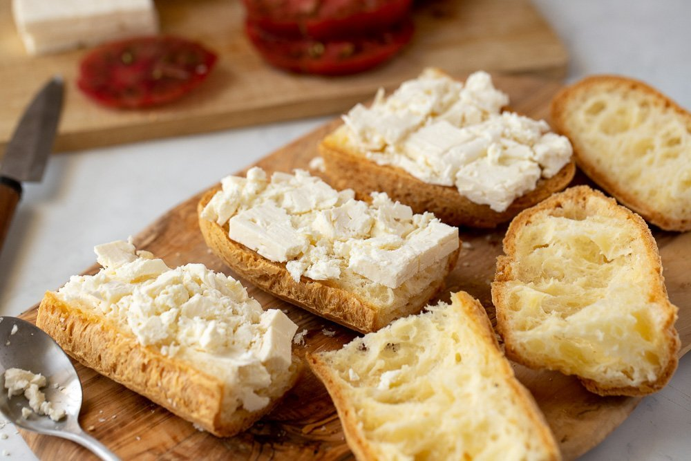 cut gluten free baguette with feta on wood board. Spoon on left and cutting boars with sliced tomato and feta in background.