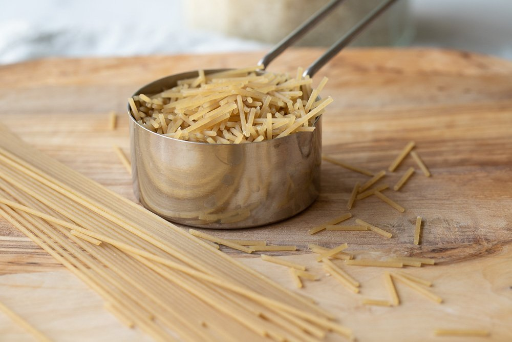 metal measuring cup with broken gluten free capellini on wood board.