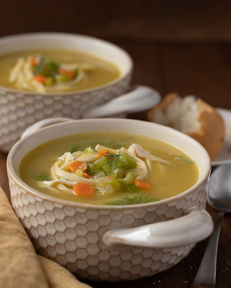 large crock bowl with gluten-free chicken noodle soup. Celery, carrot and fresh dill garnish. Gold napkin in front right. Soup bowl and plate with bread in back. Dark wood background.