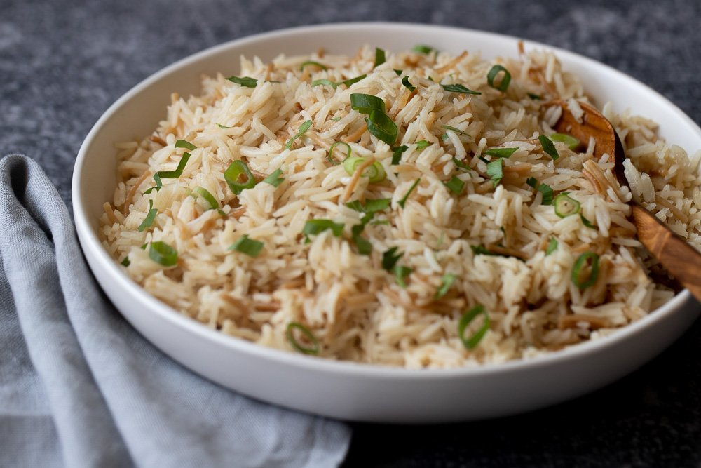 close up of white bowl with gluten free rice pilaf with noodles and topped with chopped green onion and parsley. Wood spoon in bowl on right. Gray napkin left. Gray stone background.