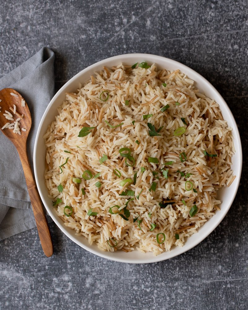 overhead view of white bowl with gluten free rice pilaf with noodles and topped with chopped green onion and parsley. Gray napkin and wood spoon on left. Gray stone background.