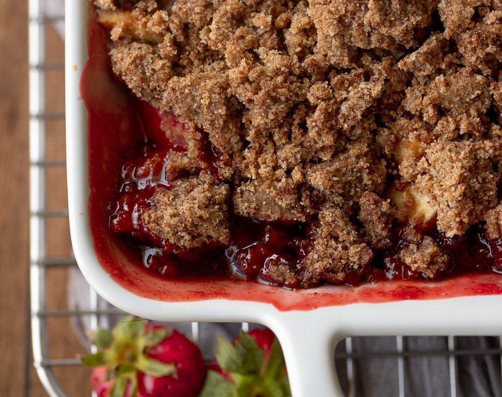 overhead view of corner of white baking dish with strawberry apple crisp. Strawberries in lower left.