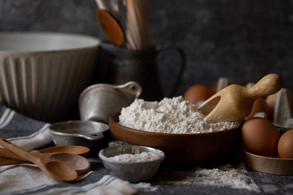 wood bowl with flour and wood scoop. wood spoons and measuring cups on left. Carton of eggs on right. Dark gray background.