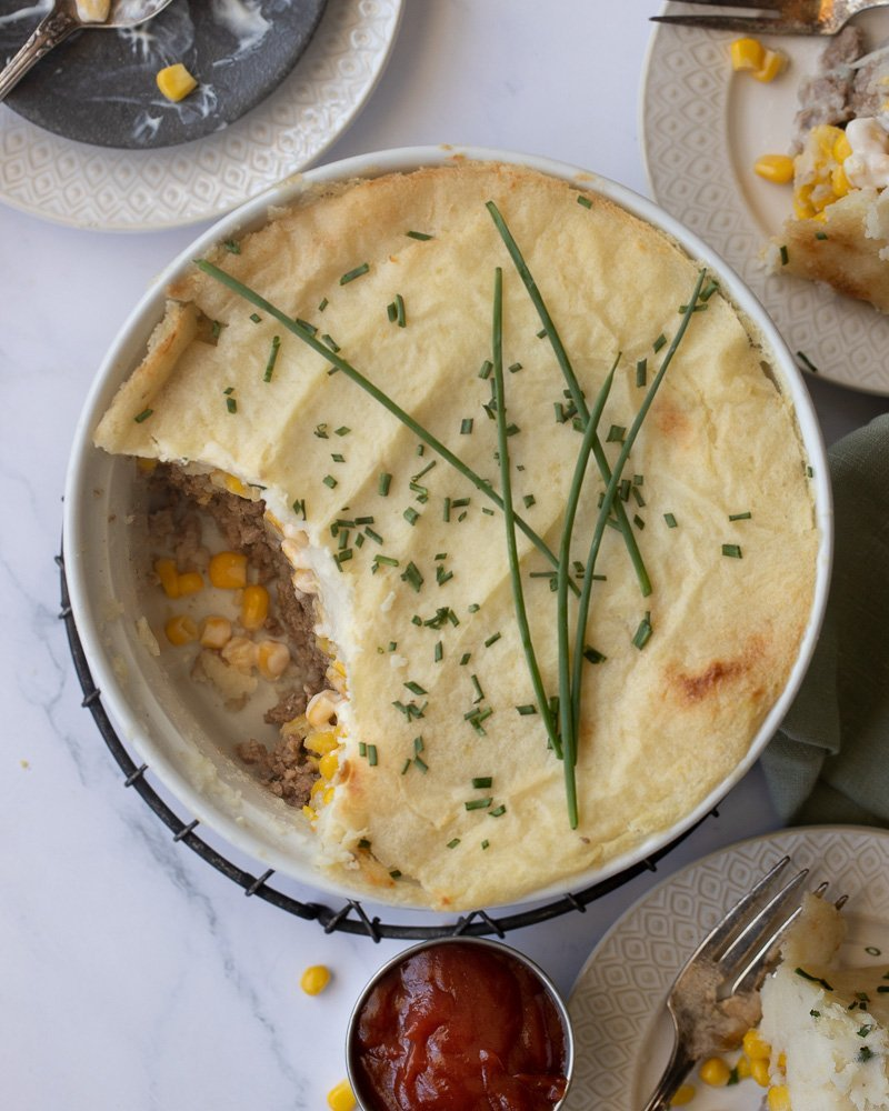 overhead view of white soufflé dish with gluten-free shepherd's pie with creamed corn on wire rack. Small white plates with shepherd's pie and fork in upper right and lower right. Green napkin on right.