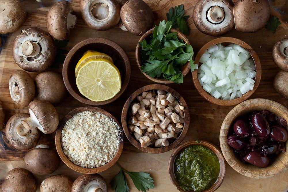 overhead view of stuffed mushrooms ingredients in wood bowls: cut lemon, parsley, chopped onion, Kalamata olives, basil pesto, chopped mushrooms, bread crumbs. Crimini mushrooms scatted around outside.