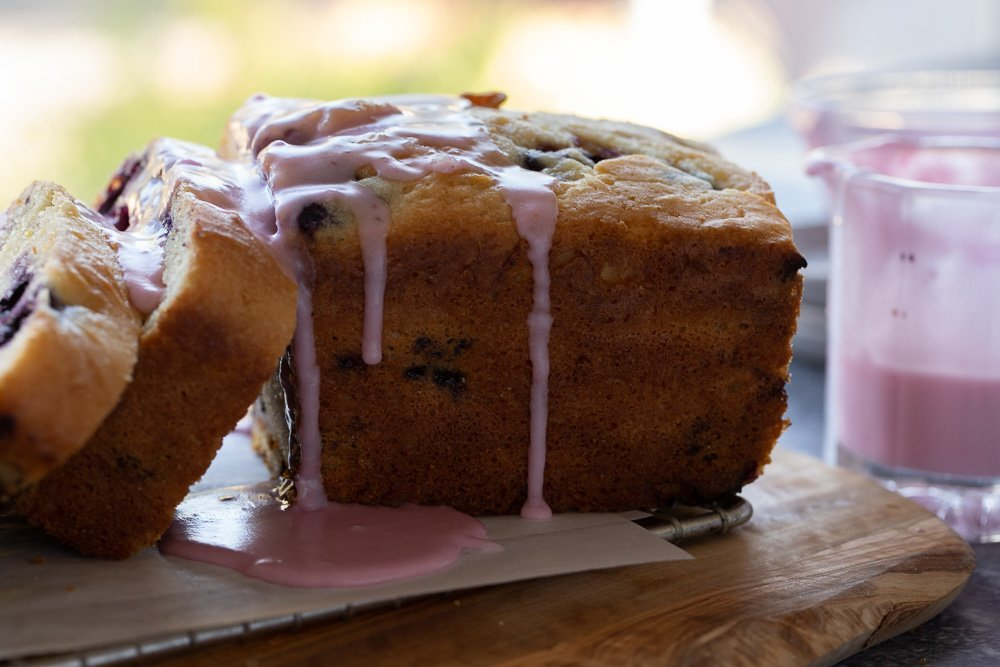 Side view of gluten-free lemon blueberry loaf on wire rack and wood board with pink icing dripping. Small glass pitcher with icing on right.