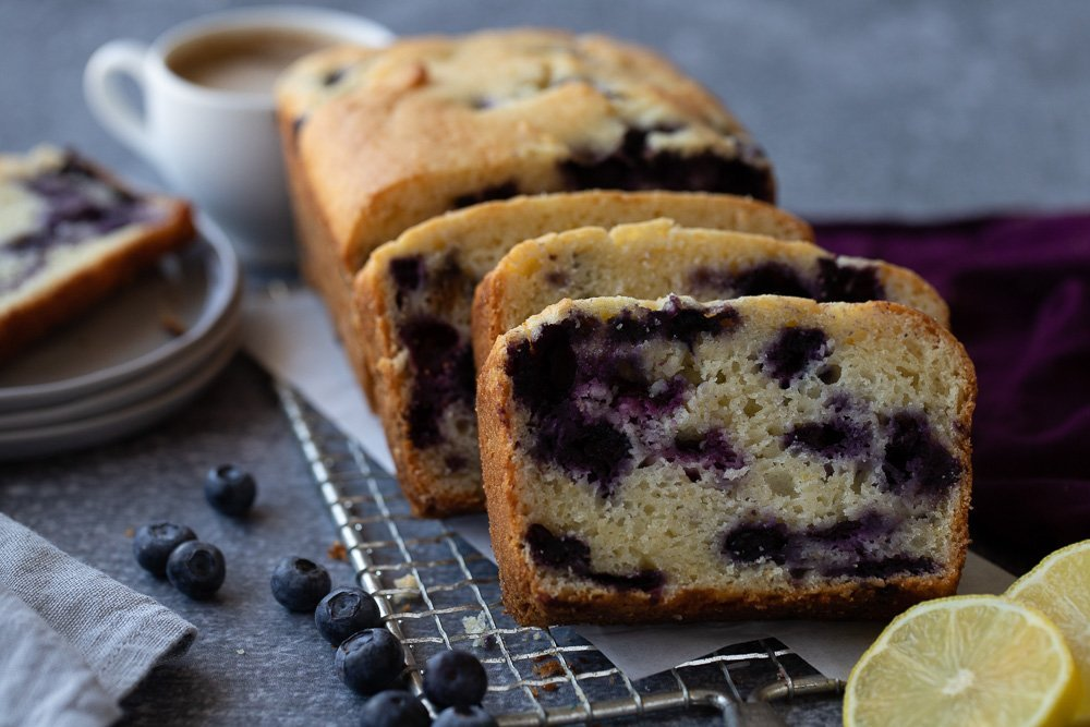 Sliced gluten-free lemon blueberry loaf on wire rack. Sliced lemon in right front. Purple napkin on right. Blueberries scattered on left. Stack of plates with slice of bread and coffee cup in background.