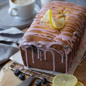 Loaf of gluten free lemon blueberry bread with pink icing drizzle on wood board. Lemon slices and blueberries in front. Coffee cup, stack of plates and milk bottle in background.