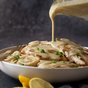 small glass pitcher pouring lemon cumin sauce onto bowl of pasta and chicken. Lemon slices in front. Dark gray background.