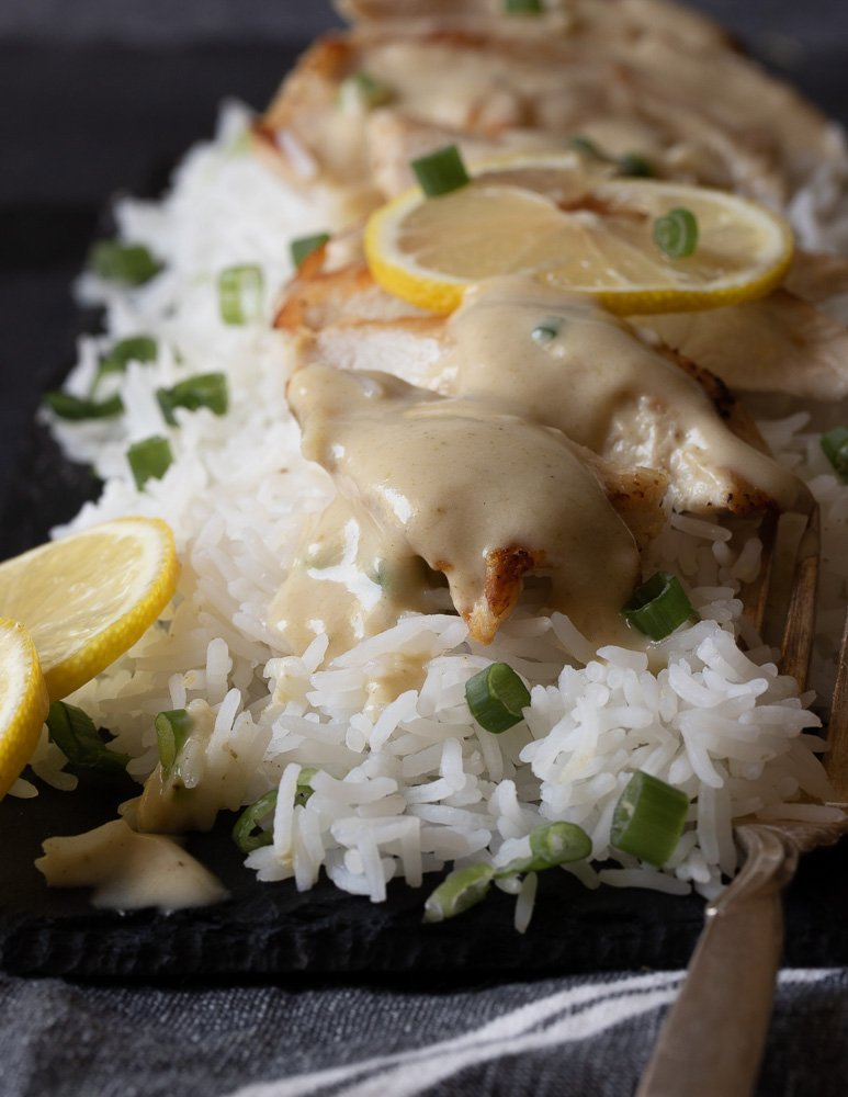 close up of lemon cumin chicken with green onion garnish on a bed of rice on black platter. Fork on right, lemon slices on left. Dark background.